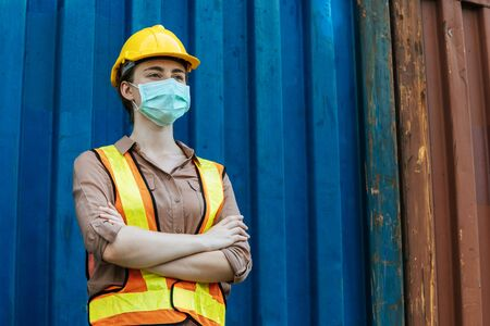 caucasian female docker or engineer control worker crossed arms wearing protection face mask standing with cargo container in background at cargo harbor, industrial, logistic import and export concept 版權商用圖片 - 148701593