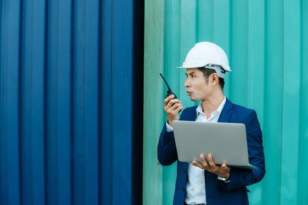 engineer control worker talking on walkie talkie and working on digital laptop computer standing with cargo container in background at cargo harbor, industrial, logistic import and export concept 版權商用圖片