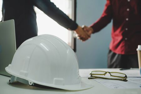 Partnership. white safety helmet on workplace desk with construction worker team hands shaking after start up plan new project contract in office room at construction site, contractor meeting concept 版權商用圖片