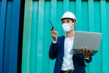 engineer control worker wearing protection face mask working on walkie talkie and digital laptop standing with container in background at cargo harbor, industrial, logistic import and export concept 版權商用圖片