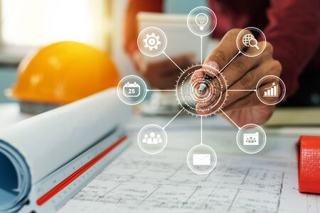 hands of group engineer and architect working on blueprint and safety helmet with virtual digital icon in meeting room at construction site office, contractor, engineering and construction concept 版權商用圖片