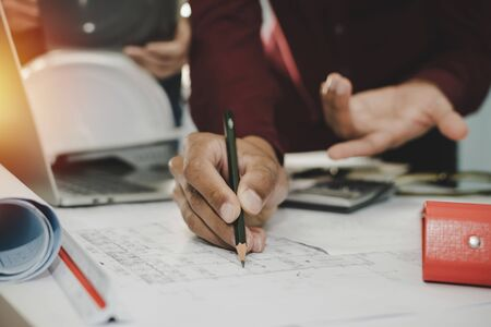 hands of group engineer and architect working on blueprint and laptop computer on workplace desk in meeting room project at construction site office, contractor, engineering and construction concept