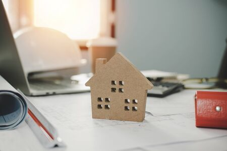 wooden house model on blueprint and tools on workplace desk for construction worker team working in office center at construction site building, architect, engineer, real estate and contractor concept