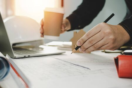 architect, engineer or interior designer hands drawing with pencil on blueprint and holding coffee cup on workplace desk in office center at construction site, construction and architectural concept