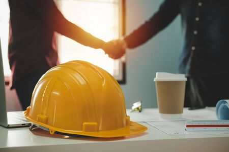 Contractor. yellow safety helmet on workplace desk with construction worker team hands shaking greeting start up plan new project contract in office center at construction site, partnership concept 版權商用圖片