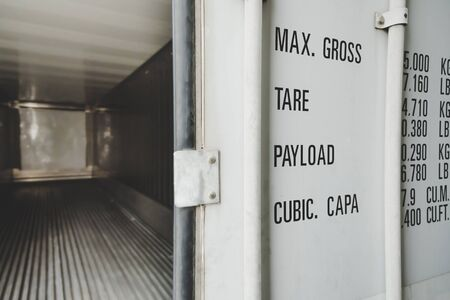 detail of white open door empty shipping cargo container for transportation shipping and logistic with copy space at container cargo harbor, industrial, logistics import and export business concept
