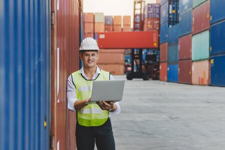 caucasian white businessman or engineer control worker working on digital laptop computer with cargo containers in background at container cargo harbor, industrial, logistic import and export concept