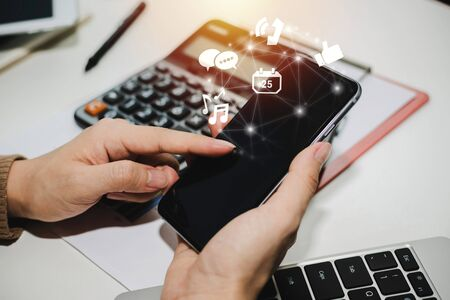 5G. hand using social network on digital mobile phone with virtual digital icon, calculator and report on desk at home office, digital marketing, work from home, business finance, technology concept