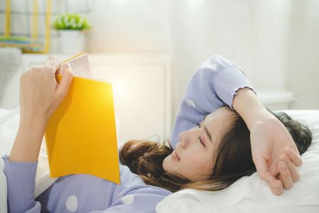 Stay Home. happy young asian pretty woman in casual clothing lying on bed and enjoying reading a book at morning in bedroom at home, joyful weekend, student, leisure, quarantine and lifestyle concept