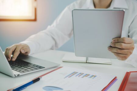 businessman in white shirt working about financial on digital mobile tablet with report document on desk at office, digital marketing, work from home, business finance, network technology concept