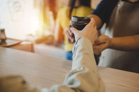hand of friendly barista serving hot coffee cup to happy female customer over counter in modern cafe coffee shop, cafe restaurant, service mind, hot coffee ,small business owner food and drink concept