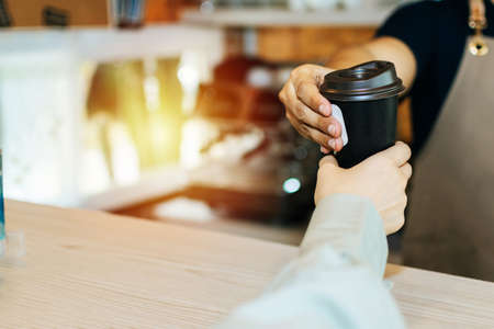 young happy handsome man barista serving hot coffee cup to friendly female customer over counter in modern cafe coffee shop, cafe restaurant, service mind, small business owner food and drink concept
