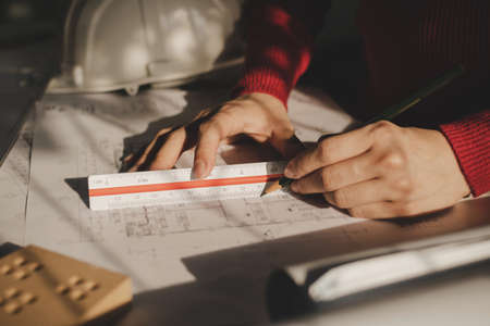 hand professional architect, engineer or interior designer drawing with ruler on blueprint on desk in office center at construction site, contractor, construction, engineering and business concept