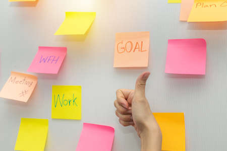 Goal. business woman showing thumbs up with colored sheets sticky note paper on white board background in office, business meeting, brainstorming, creative, digital online marketing, financial concept