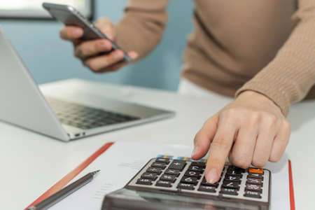 businesswoman hand calculate about financial cost bill with calculator and working on digital mobile phone and laptop computer on desk at home office, digital marketing, business finance concept