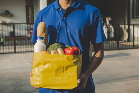 handsome food delivery service man in blue uniform holding fresh food set bag waiting for customer at door home, express delivery, self quarantine, virus outbreak, takeaway and food delivery concept 版權商用圖片