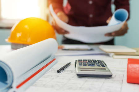 construction working tool, calculator, blueprint and safety helmet on architect workplace desk with architect in meeting room office center at construction site, construction, engineering tool concept