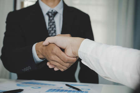 Partnership. two business man investor handshake deal with partner after finishing up business meeting on desk in meeting room office, financial, teamwork, job interview, contract agreement concept