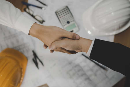 top view of architect, construction worker team hands shaking after plan project contract on workplace desk in meeting room office at construction site, contractor, partnership, construction concept