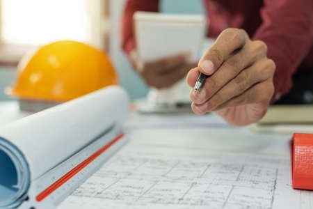 hand interior designer, engineer or architect drawing on blueprint with safety helmet in meeting room at construction site office, interior design, contractor, engineering and construction concept