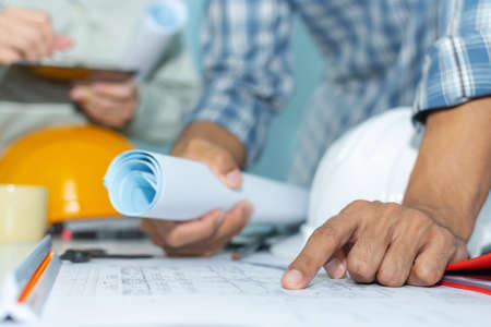 group interior designer and architect planning and working on blueprint with safety helmet in meeting room at construction site office, interior design, contractor, engineering, construction concept