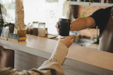 Takeaway. young friendly barista serving black hot coffee cup to female customer over counter in modern cafe coffee shop, cafe restaurant, service mind, small business owner, food and drink concept
