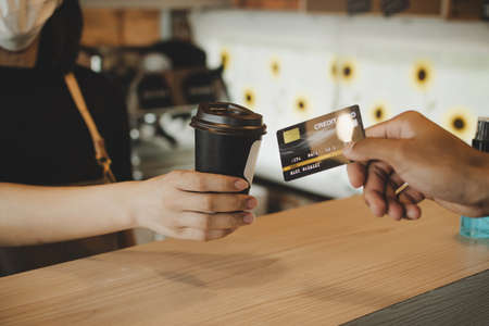 hand customer paying with credit card for buying hot coffee cup on counter in modern cafe coffee shop, cafe restaurant, digital payment, small business owner, takeaway food, food and drink concept