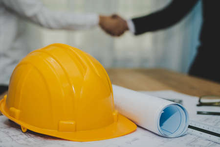 Partnership. yellow safety helmet on workplace desk with construction worker team hands shaking after start up plan new project contract in office room at construction site, contractor meeting concept