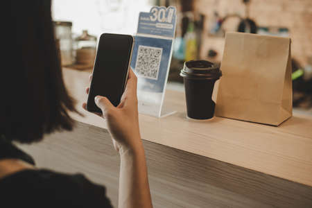 woman customer using digital mobile phone scan QR code pay for buying coffee in modern cafe coffee shop, cafe restaurant, digital payment, online shopping, takeaway food, internet technology concept Imagens