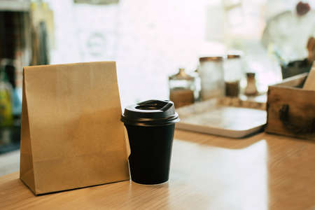 hot black coffee cup and dessert paper set bag waiting for customer on counter in modern cafe coffee shop, food delivery, cafe restaurant, takeaway food, small business owner, food and drink concept Imagens