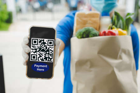 food delivery service man hand showing QR code on digital mobile phone and holding fresh food set bag waiting for customer at door home, digital payment technology and fast food delivery concept