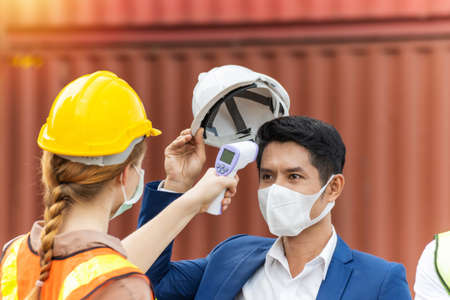 industrial worker woman temperature checking fever by digital thermometer with businessman with cargo container in background at container cargo harbor, industrial, logistic import and export concept
