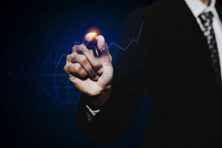 businessman investor hand pointing with pen on virtual graphic graph chart screen on dark background, stock market, investment, digital technology, trading statistics and business strategy concept