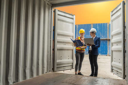 industrial worker woman and engineer control worker checking in front door of cargo container at container cargo harbor, transport, industrial, logistic, transportation, import and export concept 版權商用圖片
