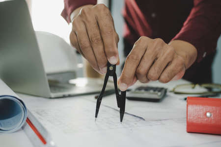 professional architect or interior designer hands drawing with divider compass on blueprint on desk in meeting room office at construction site, construction industrial, engineering business concept