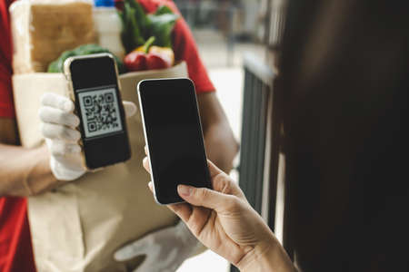 hand customer using digital mobile phone scan QR code paying for buying fresh food set bag from food delivery service man, express delivery, digital payment technology and fast food delivery concept