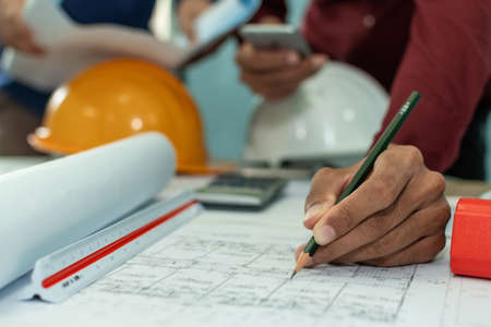 group of professional architect or interior designer hands drawing with pencil on blueprint on desk in meeting room office at construction site, construction industrial, engineering business concept