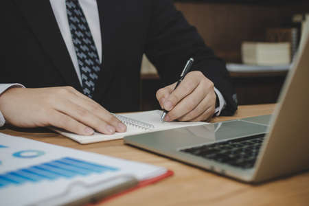 attractive business man in black suit working and writing on document report on desk in meeting room at home office, investment, contract, digital online marketing and financial business concept 版權商用圖片