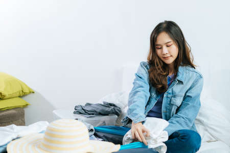 young asian pretty woman traveler hipster prepare and packing clothes into suitcase for holiday vacation on bed at home, long weekend, summer holiday, backpacker, travel and lifestyle concept Imagens