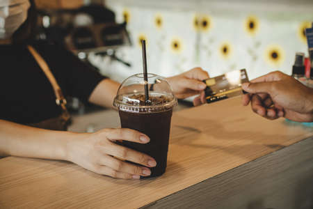 hand customer paying with credit card for buying ice black coffee on counter in modern cafe coffee shop, cafe restaurant, digital payment, small business owner, takeaway food, food and drink concept