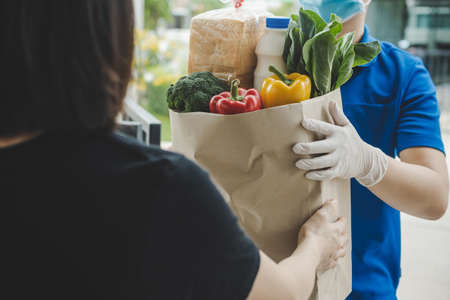 food delivery service man in blue uniform wearing protection face mask holding fresh food set bag to customer at door home, express delivery, quarantine, virus outbreak, takeaway food delivery concept Imagens