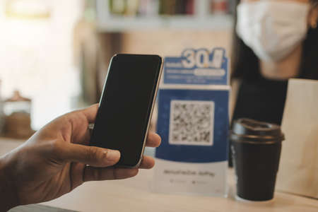 customer hand using digital mobile phone scan QR code pay for buying coffee in modern cafe coffee shop, cafe restaurant, digital payment, online shopping, takeaway food, internet technology concept