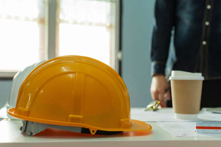 yellow safety helmet and coffee cup on workplace desk with architect or engineer standing in meeting room office center at construction site, contractor meeting, engineering and construction concept