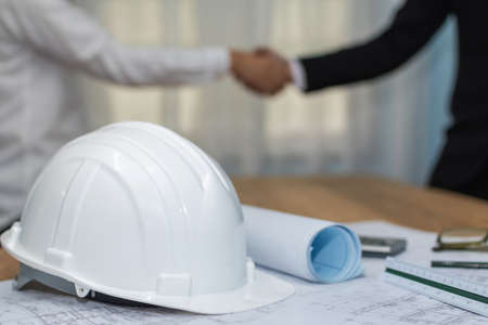 contractor. white safety helmet on workplace desk with construction worker team hands shaking after start up plan new project contract in office room at construction site, partnership meeting concept Imagens