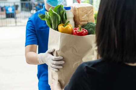 woman customer receiving fresh food set bag from food delivery service man wearing protection glove and face mask in red uniform, express delivery, quarantine, virus outbreak, food delivery concept