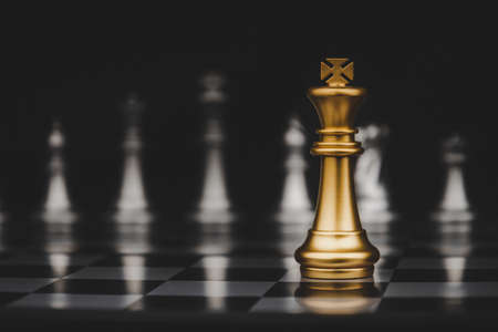 Leadership. gold king with silver chess pieces on chess board game competition on dark background, chess battle, victory, success, management, team leader, teamwork and business strategy concept Imagens