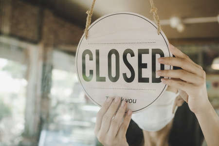 Closed, waitress woman wearing protection face mask turning open sign board on glass door in modern cafe coffee shop, cafe restaurant, retail store, small business owner, food and drink concept Imagens