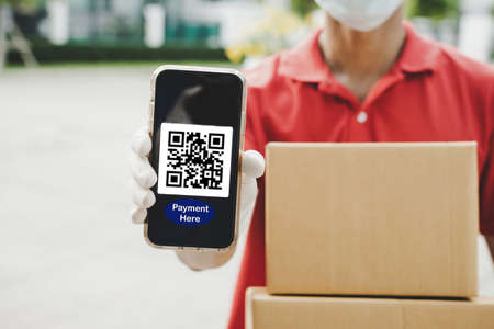 fast delivery service man hand showing QR code on digital mobile phone and holding parcel post box waiting for customer at door home, digital payment technology and fast food delivery concept