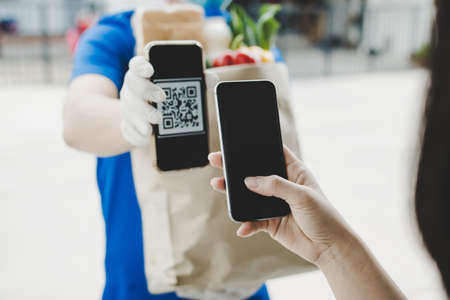 woman customer using digital mobile phone scan QR code paying for buying fresh food set bag from food delivery service man, express delivery, digital payment technology and fast food delivery concept Imagens