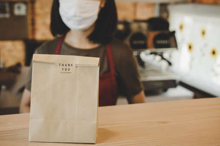 dessert paper set bag on counter bar with waitress woman waiting for customer in modern cafe coffee shop, food delivery, cafe restaurant, takeaway food, small business owner, food and drink concept